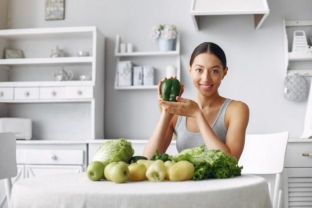 Красивая и спортивная женщина на кухне с овощами