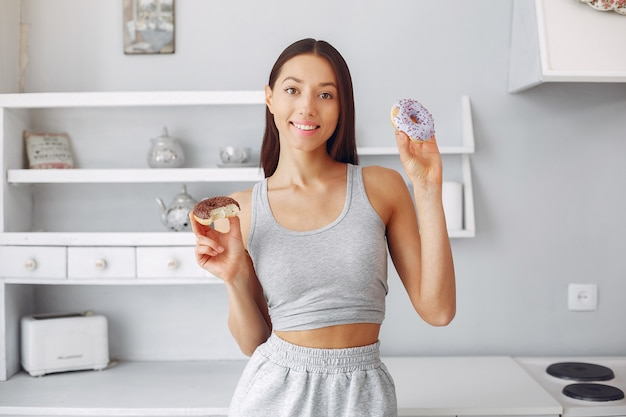 Красивая женщина, стоя на кухне с пончик
