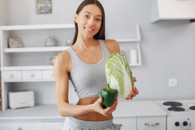 野菜とキッチンで美しく、スポーティな女性