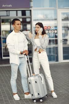 Красивая пара стоит возле аэропорта