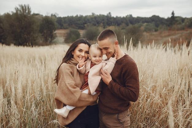 Милая и стильная семья играет в осеннем поле