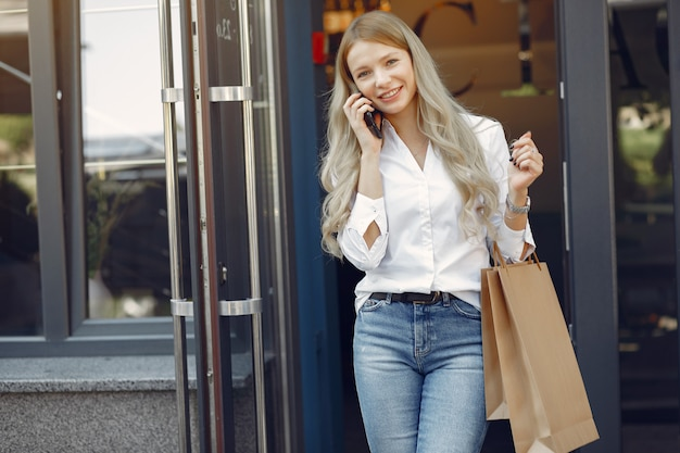 街で買い物袋を持つエレガントな女の子