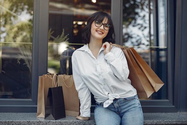 ショッピングバッグと通りのエレガントでスタイリッシュな女の子