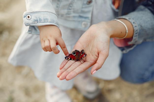 Дочь трогает бабочку