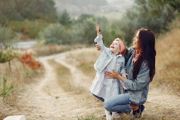 フィールドで遊ぶ幼い娘を持つ母