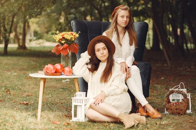 公園の椅子に座っているエレガントでスタイリッシュな女の子