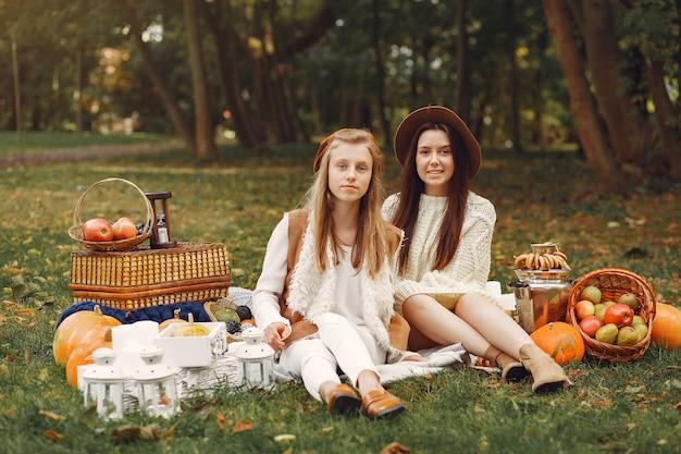 Элегантные и стильные девушки сидят в парке