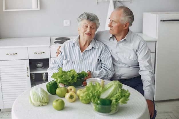 美しい老夫婦は、キッチンで食事を準備します