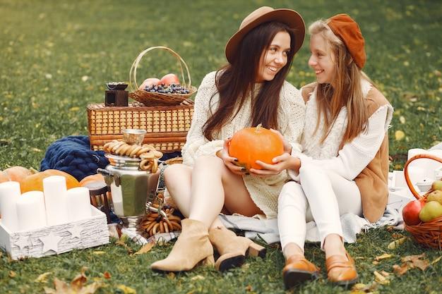 秋の公園に座っているエレガントでスタイリッシュな女の子