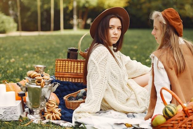 Элегантные и стильные девушки сидят в осеннем парке