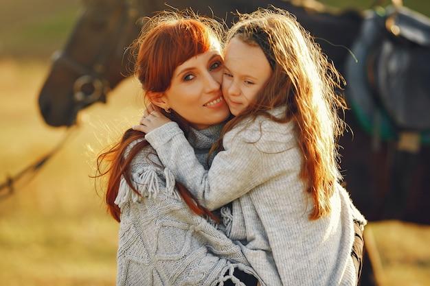 Мать и дочь в поле, играя с лошадью