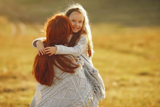 秋のフィールドで遊ぶ幼い娘を持つ母