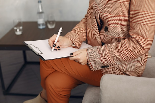 Психолог в очках сидит на стуле в офисе