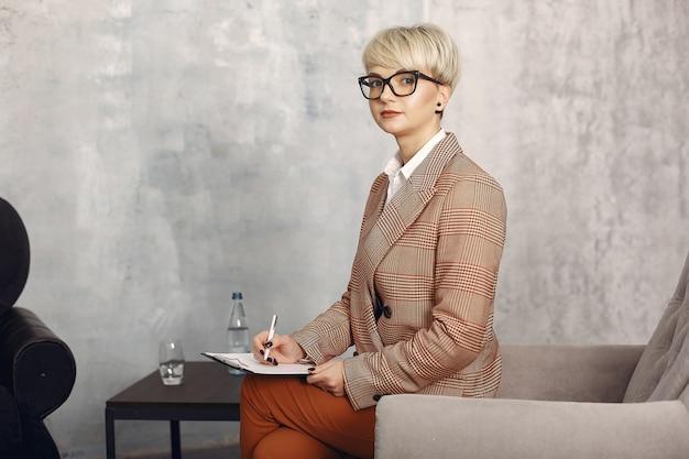 オフィスで椅子に座ってメガネの心理学者