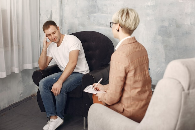 心理学者のオフィスに座っていると問題について話している男