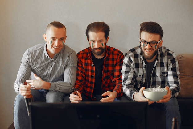 ファンのグループはテレビでサッカーを見ています
