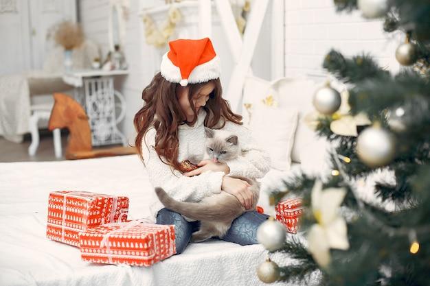 Маленькая девочка сидит на кровати с милой кошечкой