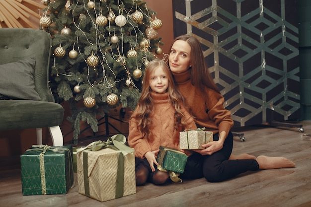 クリスマスツリーの近くのかわいい娘を持つ母