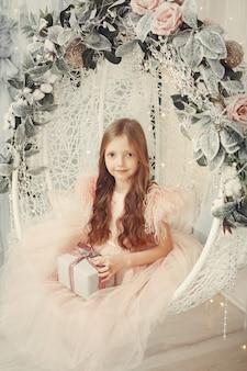 ピンクのドレスでクリスマスツリーの近くの小さな女の子