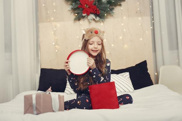 青いパジャマでクリスマスツリーの近くの小さな女の子