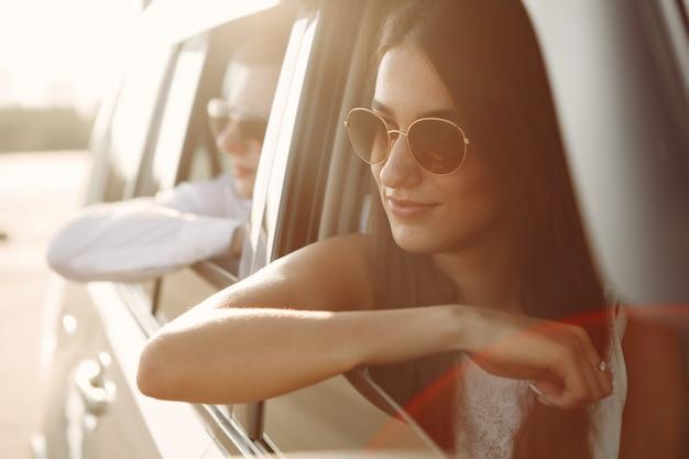 美しいカップルは車に座っている夏の公園で時間を過ごす