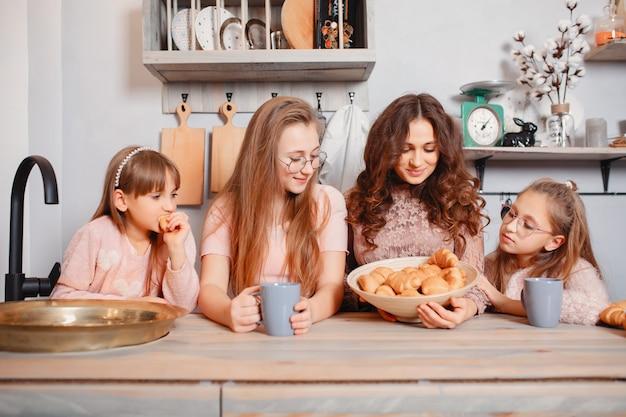 Милые сестры стоя на кухне и ест булочки