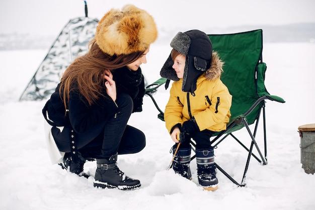 息子と冬の釣りに座っている美しい女性