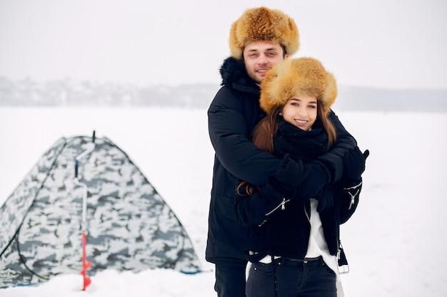 氷の上に冬服を着て立っているカップルを愛する