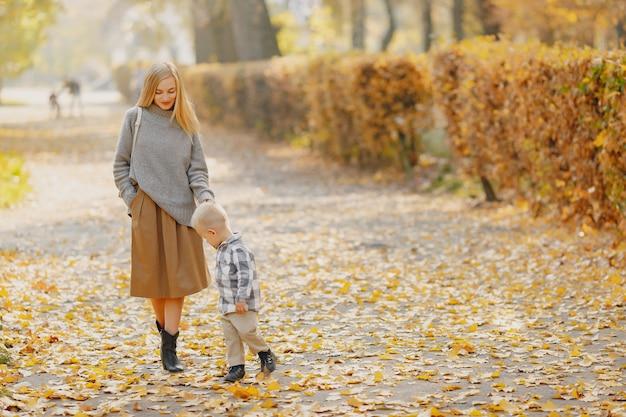 Мать с маленьким сыном, играя в осеннем поле