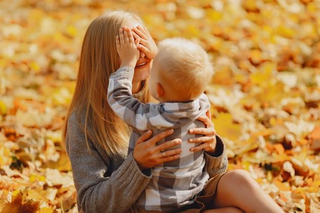 Мать с маленьким сыном сидит в осеннем поле