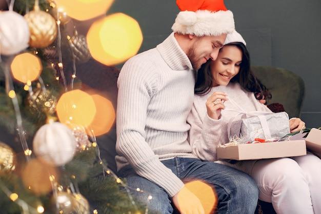 クリスマスツリーの近くに自宅で座っているかわいい家族