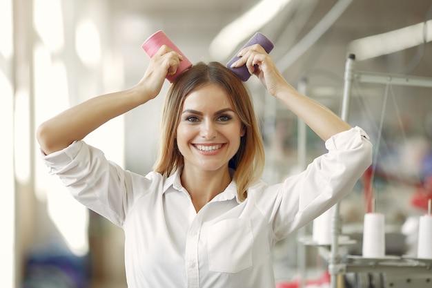 Женщина стоит на фабрике с резьбой