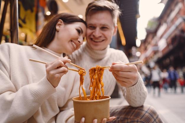 上海の食品市場の外で箸で麺を食べる新婚カップル