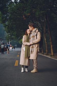 Новобрачная пара, показывая привязанность и держась за руки, когда они идут через национальный лесной парк чжанцзяцзе