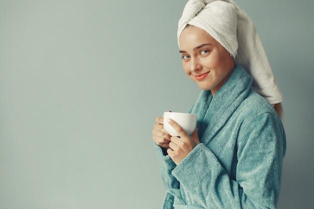 青いバスローブで立っている美しい少女