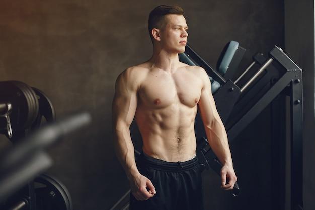 Красивый мужчина занимается в тренажерном зале