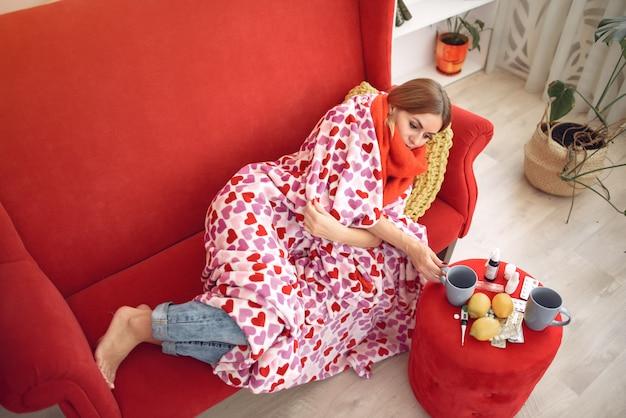 風邪で家に座って、熱いお茶を飲む女性