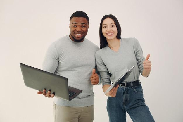 Молодые иностранные люди работают вместе и используют ноутбук