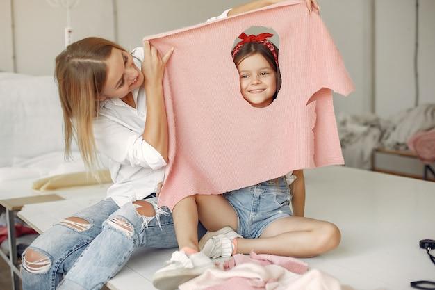 Мама с маленькой дочкой измеряют ткань для шитья