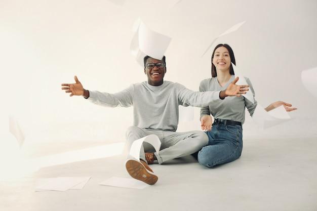 Молодые иностранные люди сидят с документами в студии