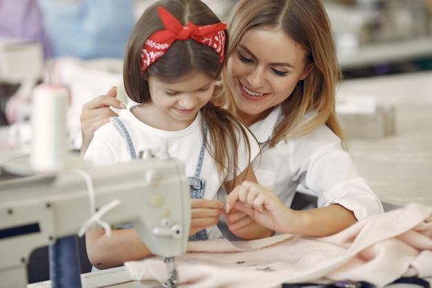 Мама с маленькой дочкой шьют одежду на фабрике