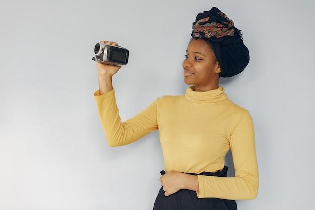 Милая черная женщина, стоя на белой стене
