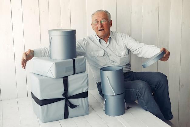 Элегантный старик сидит дома с рождественскими подарками