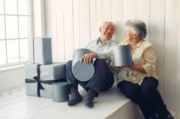 クリスマスプレゼントで自宅で座っているエレガントな老夫婦