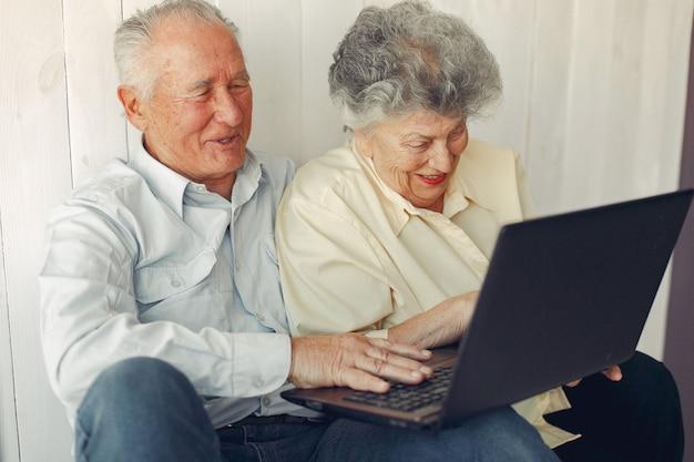 自宅で座っているとラップトップを使用してエレガントな老夫婦