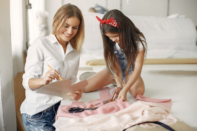 小さな娘を持つ母は、裁縫用の生地を測定します。