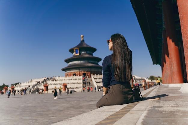 Брюнетка сидит на ступеньках у храма хевен в китае