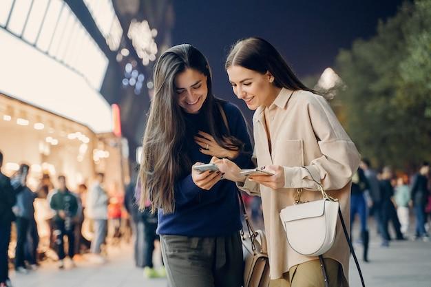 Две подружки пользуются мобильным телефоном, исследуя новый город ночью
