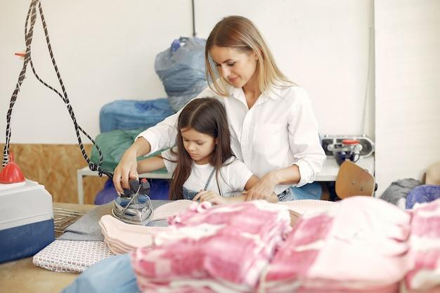 Мама с маленькой дочкой гладят ткань на фабрике
