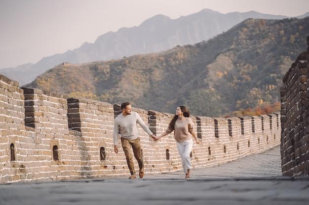 万里の長城で実行しているとジャンプの美しい若いカップル。